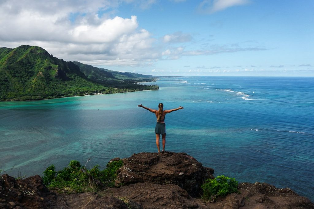 Woman Standing on top of Crouching Lion on Oahu overlooking the ocean