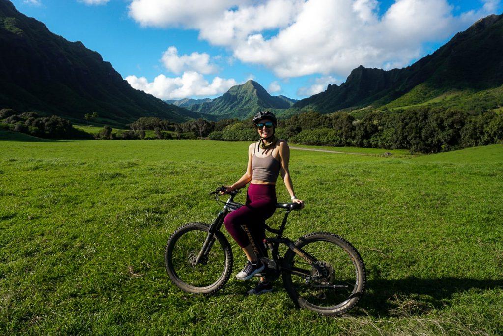 Woman on bike standing in Kualoa Ranch