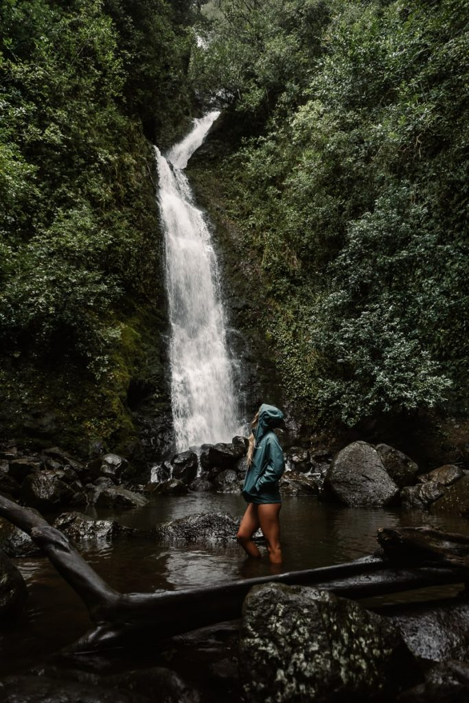 Woman standing in the water looking up at 50 foot Lulumahu waterfall