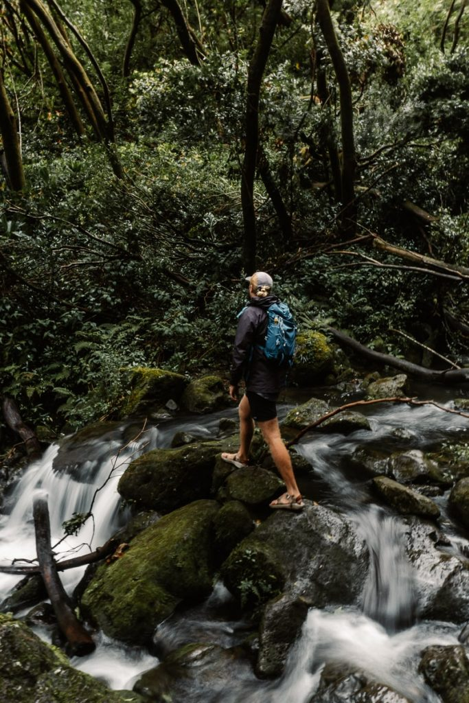 Man crossing a rocky stream with a tiny waterfall