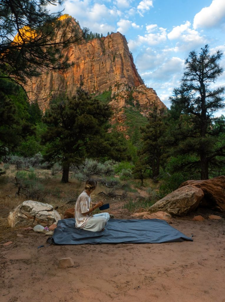 Woman sitting on a tarp eating looking out at the moutains
