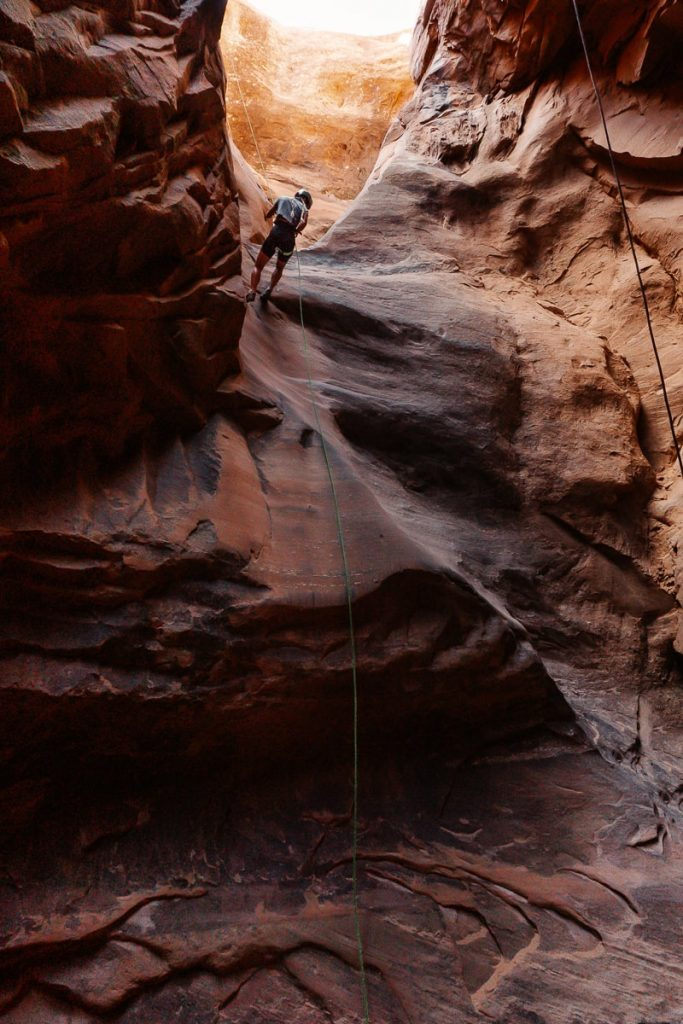 Woman repelling into a red canyon in Zion National Park