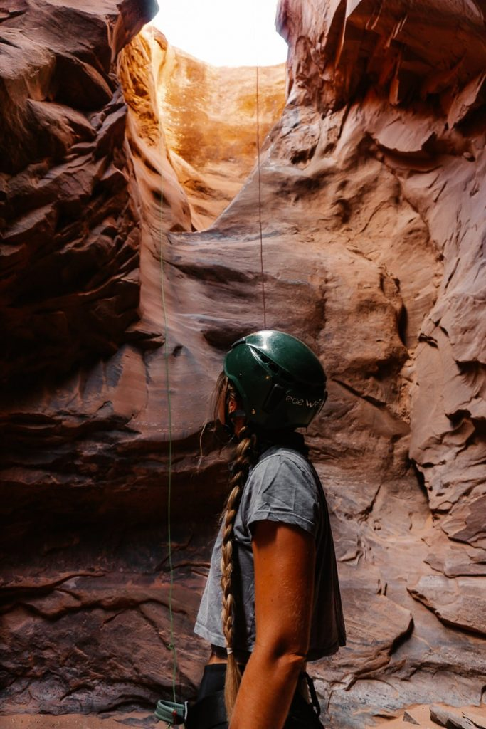 Woman in a climbing helment looking up at the rock in Moab