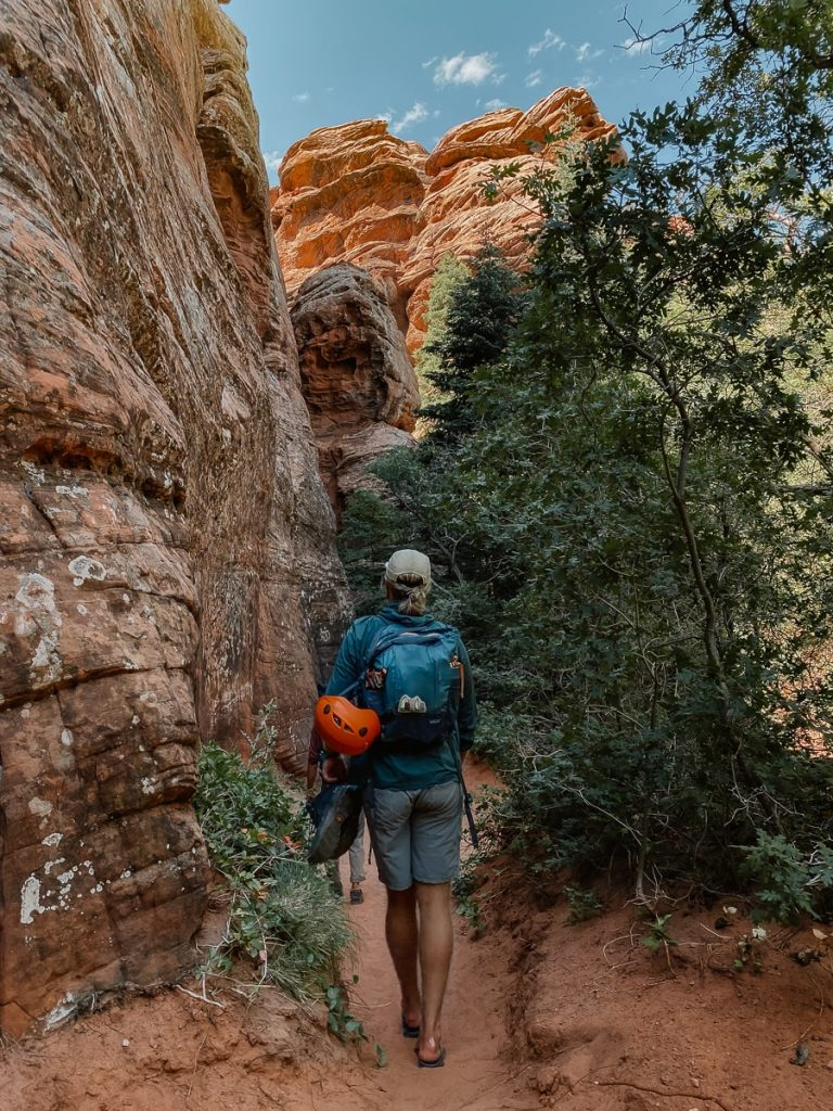 Man walking on trail surrounded by red cliffs.