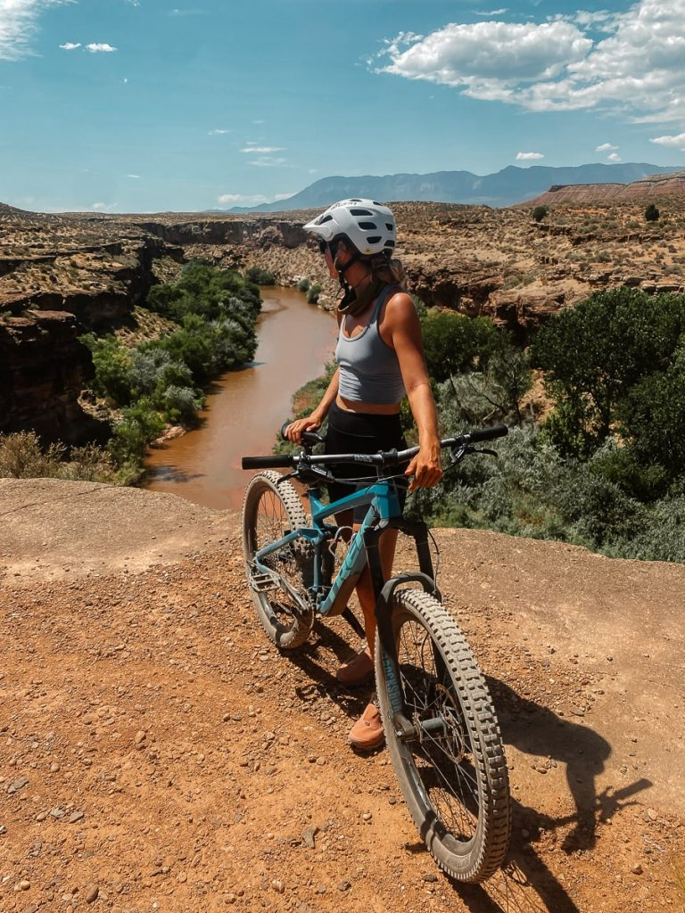 Woman standing behind a mountain bike overlooking a river gulch in Zion National Park.