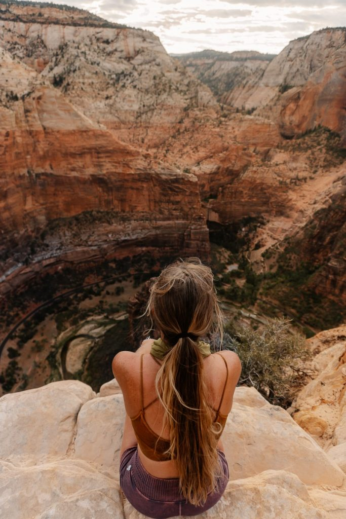 Women sitting on the edge of a cliff on Angles Landing Trail overlooking Zion National Park