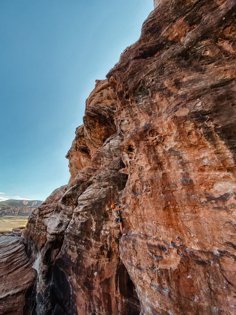 Girl rock climbing high up in Zion National park with red mountains in the background.