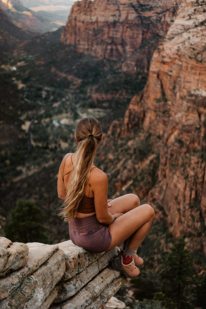 Girl sitting with her back to the camera on a ledge on Angels Landing Trail overlooking Zion National Park