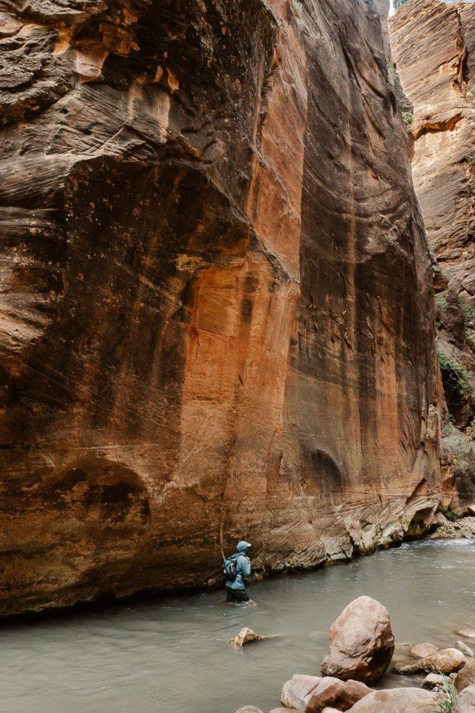 Man walking in waist deep water alongside the canyon wall in The Narrows