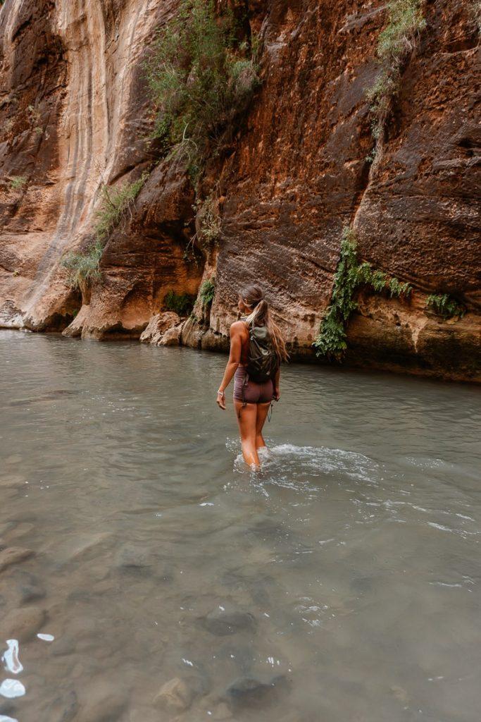 Woman hiking in knee deep water in The Narrows