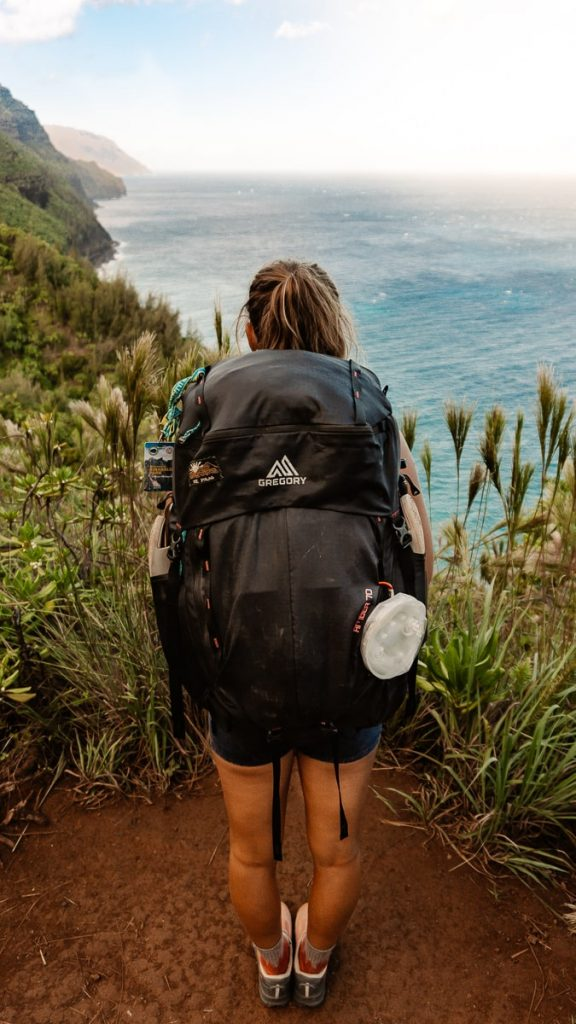 Girl standing on the Kalalau Trail with her large backpack looking out over the ocean