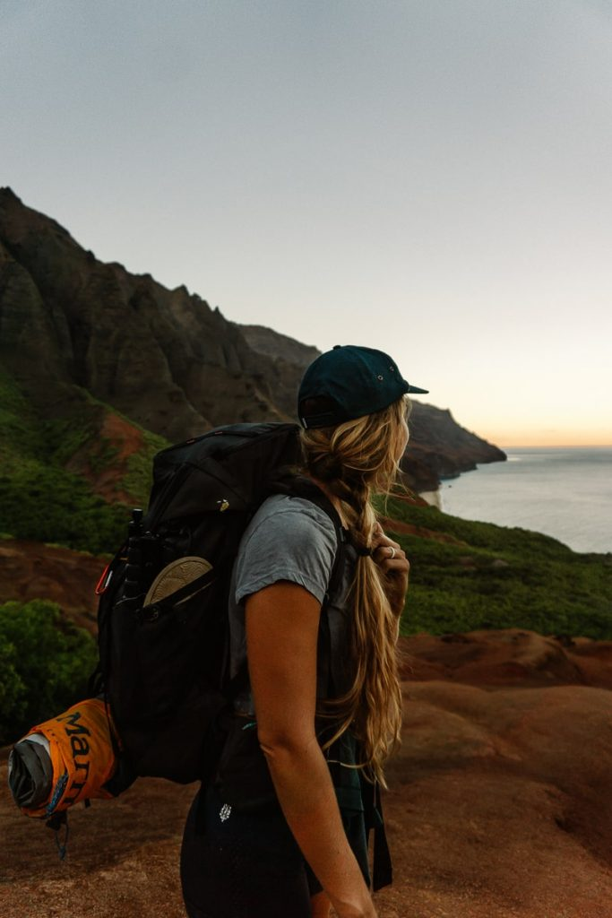 Girl standing with a large backpack on in front of the mountain and ocean at sunrise