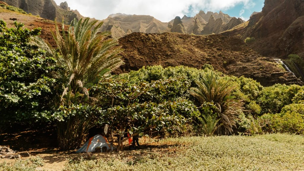 Tent on the beach with lush vegetation and cliffs in the background