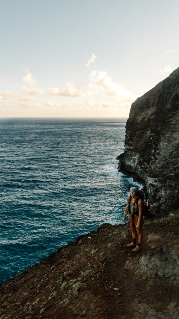 Girl standing on a ledge near the ocean while backpacking the Kalalau Trail