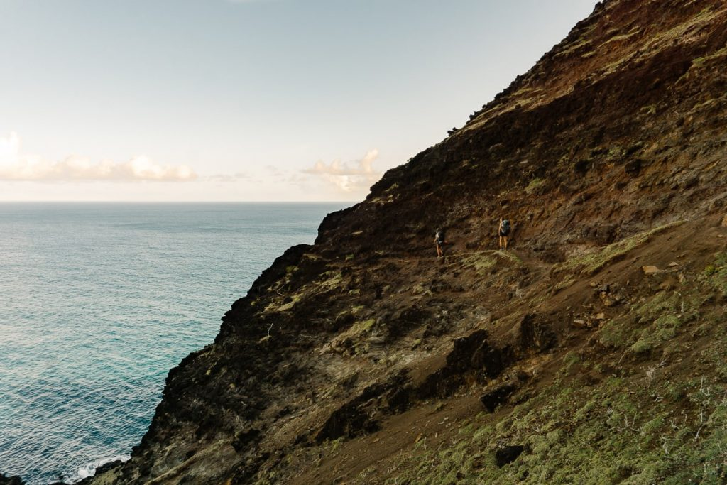Two hikers walking on a ledge overlooking the ocean on Kalalau Trail