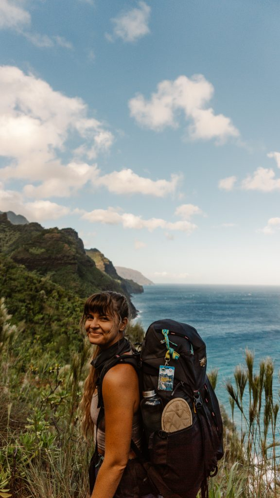 Women standing on the Kalalau Trail with beautiful views of the Na Pali Coast in the background