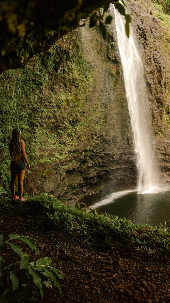 Girl standing on a lush looking down at Hanakapia'ia Falls
