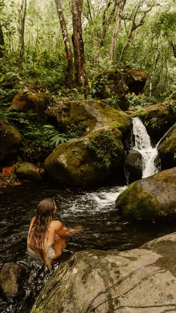 Girl sitting in a pool at the base of a small waterfall in Hanakoa
