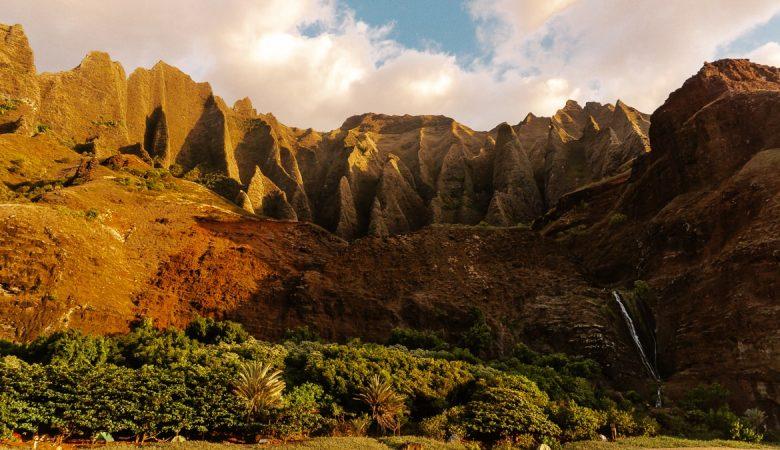 Towering greens cliffs at golden hour on the Na Pali Coast at Kalalau Beach