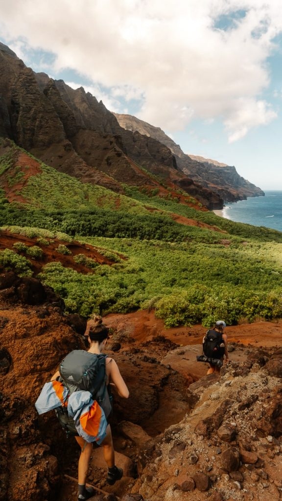 two girls hiking down a steep trail while backpacking the Kalalau Trail