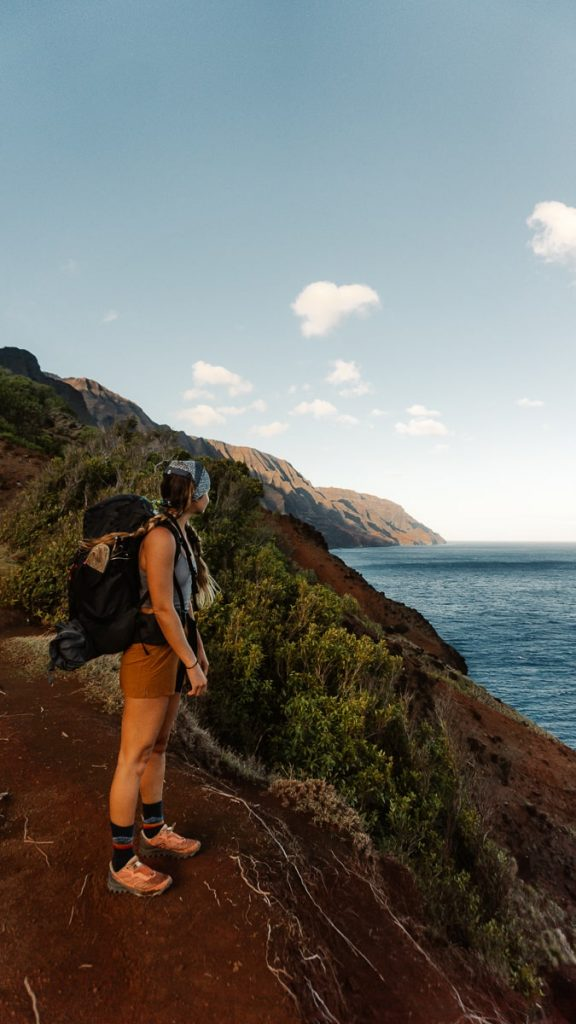 Hiker standing on the trail looking out over the ocean with mountains behind her