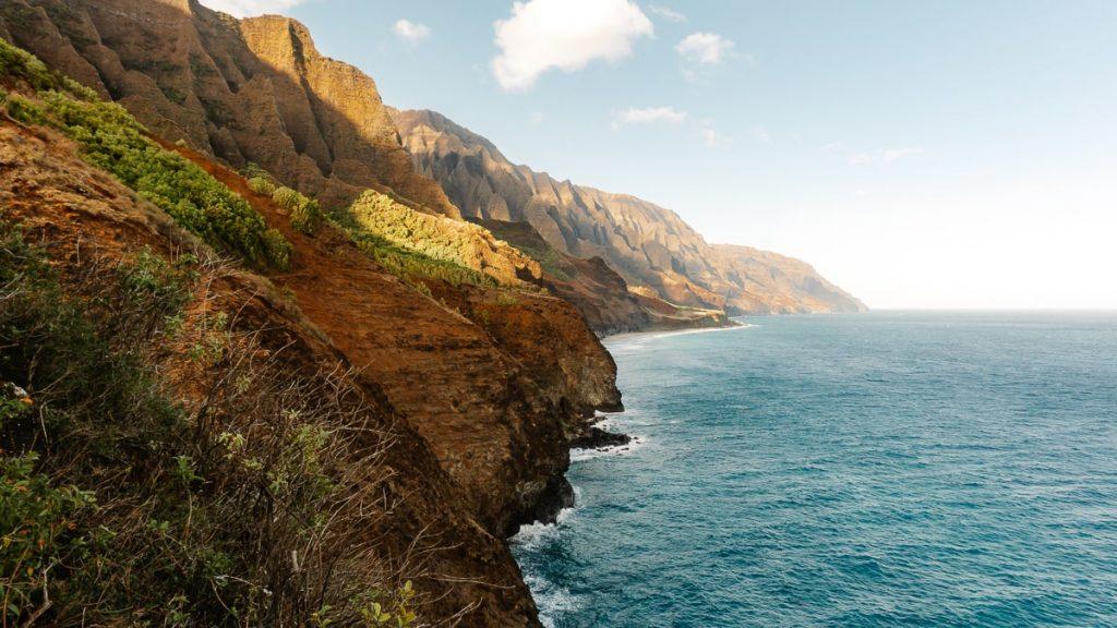 Landscape shot of green cliffs alongside teal blue waters
