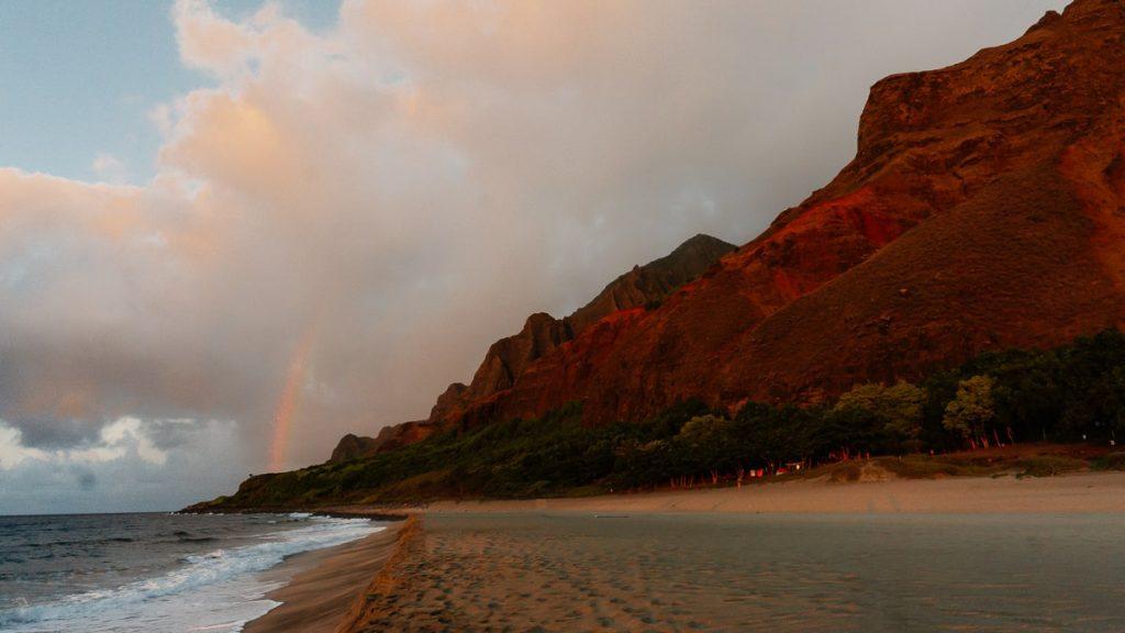 Kalalau Beach at sunset with a rainbow over the mountains