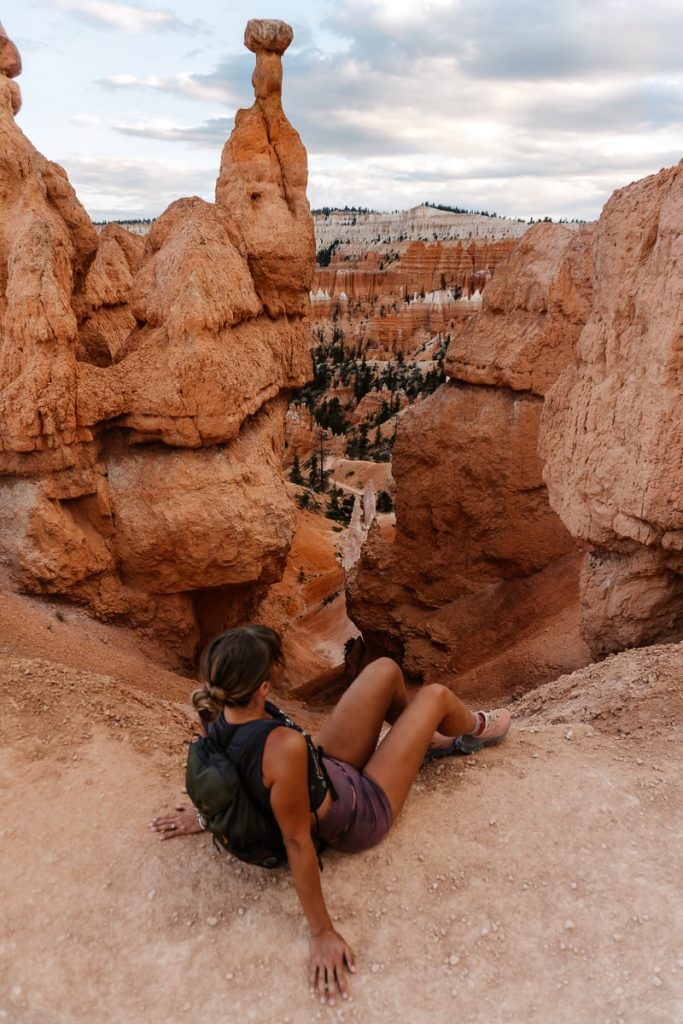 Girl sitting on the ledge of Queen's Garden trail overlooking the Bryce Canyon Amphitheater